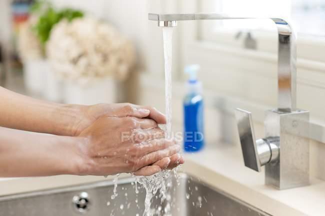 Primer plano de la mujer lavándose las manos bajo el grifo en la cocina . - foto de stock