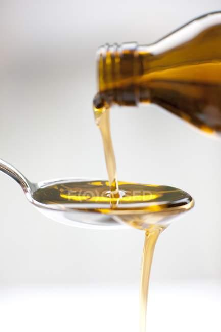 Закри розливу пляшку медицини на ложкою. — стокове фото
