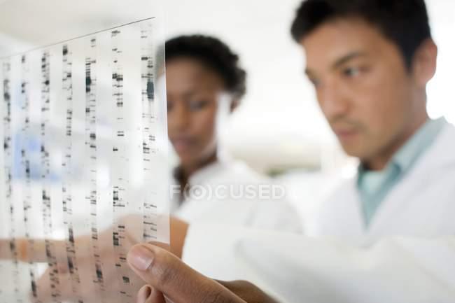 Close-up dei risultati della ricerca genetica nelle mani degli scienziati. — Foto stock