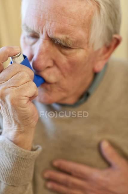 Portrait of senior man using asthma inhaler. — Stock Photo