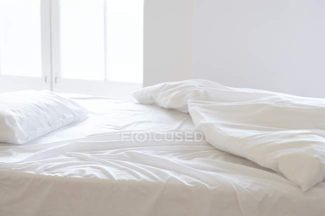 Unmade empty bed in sunlight. — Stock Photo
