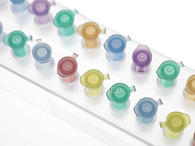 Colorful Eppendorf tubes in rack on white background. — Stock Photo