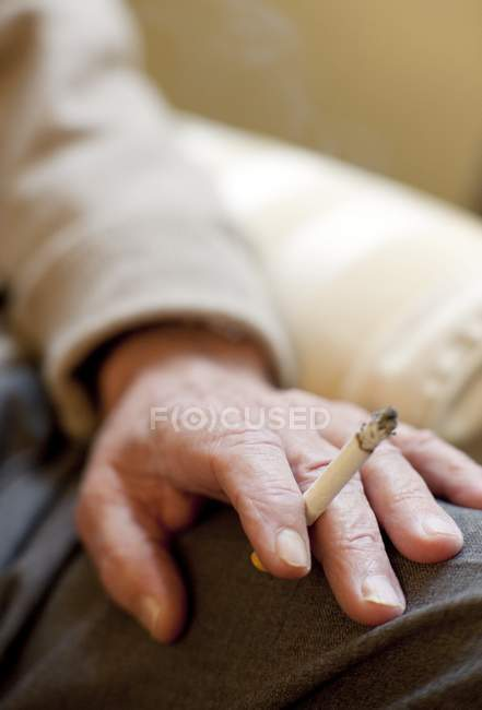 Close-up of senior man hand holding cigarette. — Stock Photo