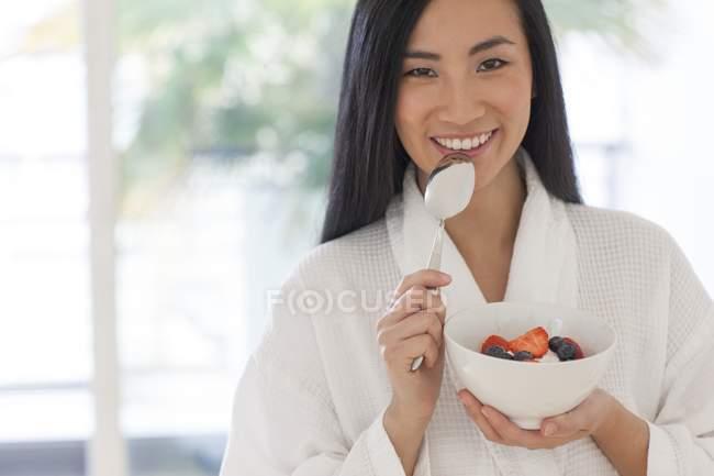 Asiatische Mitte erwachsene Frau im Bademantel hält Schüssel mit Obst und Joghurt und Löffel — Stockfoto