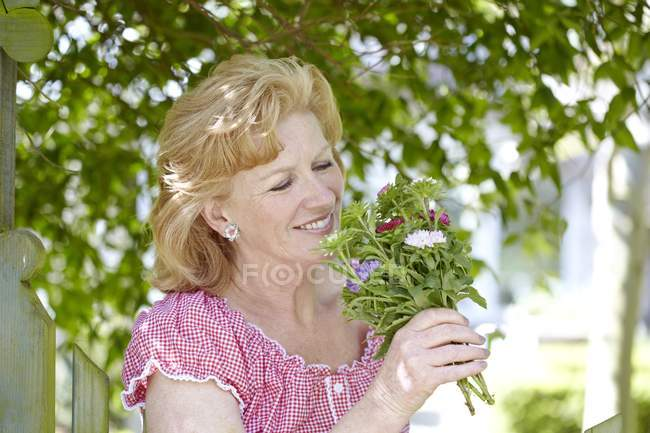 Женщина нюхает цветы на открытом воздухе — стоковое фото