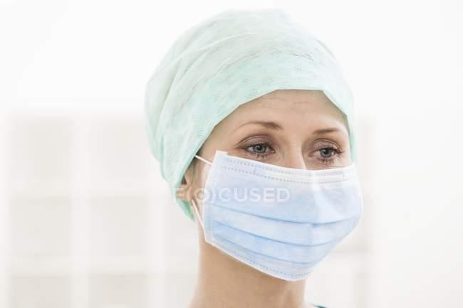 Cirujano femenino con máscara quirúrgica y gorra . - foto de stock