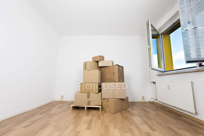 Stack of cardboard boxes in empty room. — Stock Photo