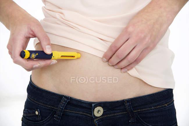 Recadrée vue de femme faisant l'injection dans l'estomac avec dispositif médical. — Photo de stock