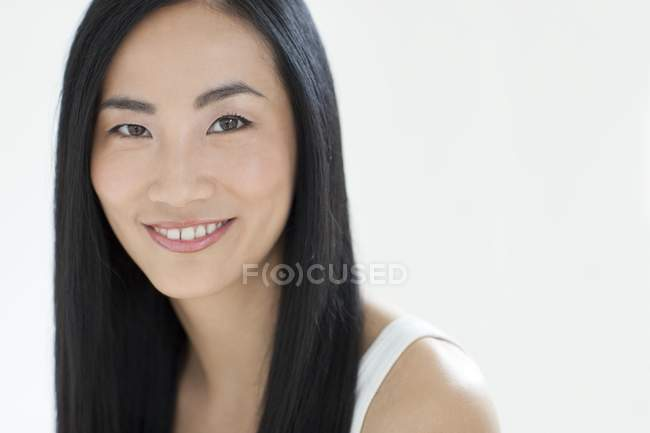 Asian mid adult woman smiling, portrait. — Stock Photo