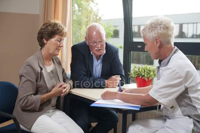 Enfermera en consulta del hospital con pacientes mayores. - foto de stock