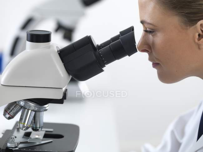 Female scientist using microscope. — Stock Photo
