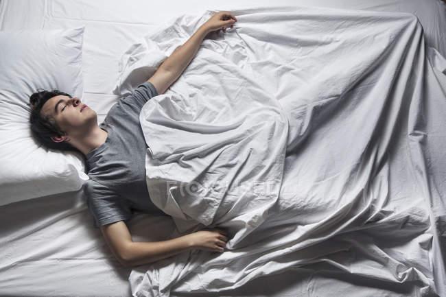 Вид сверху на молодого человека, спящего в постели . — стоковое фото