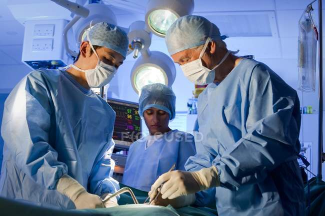 Surgical team in face masks working in operating theatre. — Stock Photo
