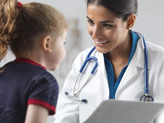 Женщины педиатр, говорить с девушкой дошкольника. — стоковое фото