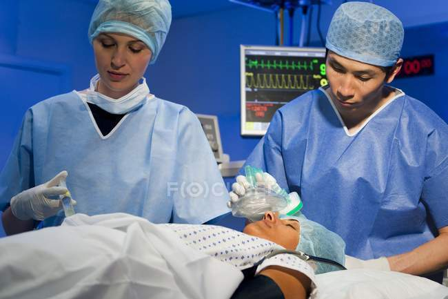 Asian surgeon adjusting anesthetic to female patient — Stock Photo
