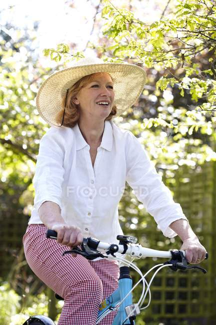 Mature woman in sunhat cycling in garden. — Stock Photo