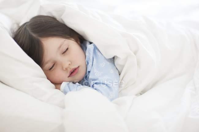Дошкільника дівчинка спить під ковдру на ліжку. — стокове фото