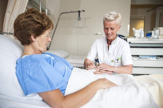 Mature nurse preparing patient for IV line. — Stock Photo
