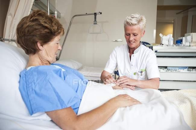 Enfermera madura preparación a paciente por vía intravenosa. - foto de stock
