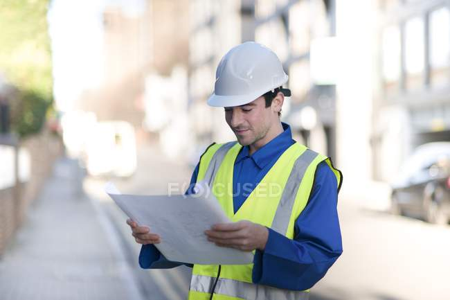 Construction worker in hard hat and high visibility jacket reading blueprint. — Stock Photo