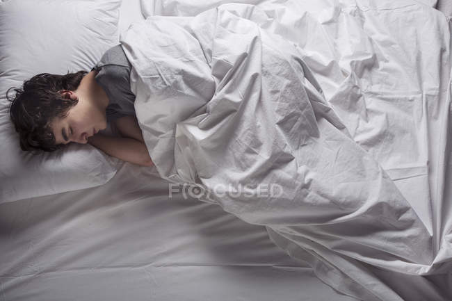 Overhead view of young man sleeping in bed. — Stock Photo