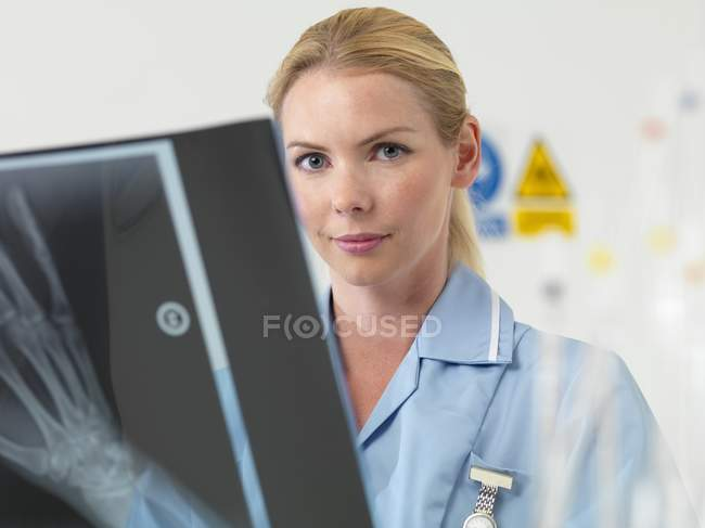 Female radiologist looking in camera while examining X-ray image. — Stock Photo