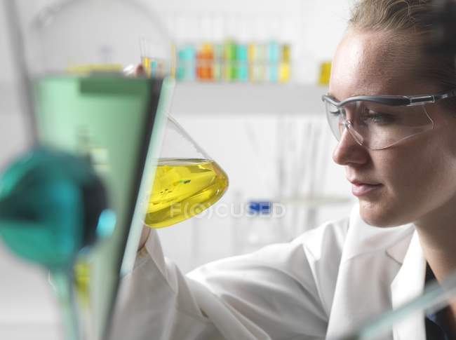 Female scientist agitating yellow liquid in flask. — Stock Photo
