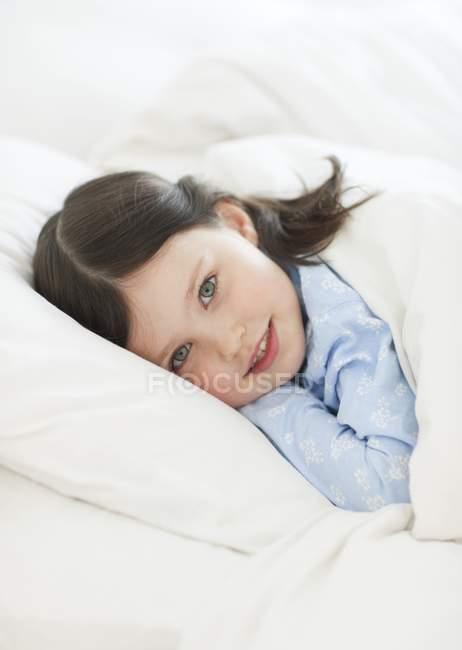 Fille d'âge préscolaire se reposant sous la couette au lit . — Photo de stock