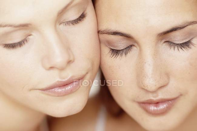 Close-up portrait of two young women with eyes closed. — Stock Photo