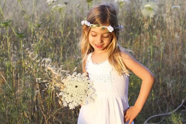 Enfant d'âge préscolaire jeune fille en robe blanche et Couronne florale dans le champ — Photo de stock
