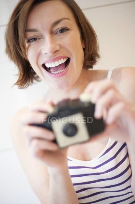 Donna tenendo la fotocamera e guardando nella fotocamera . — Foto stock