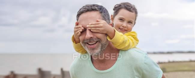 Дочка, що охоплюють батько очі руками. — стокове фото