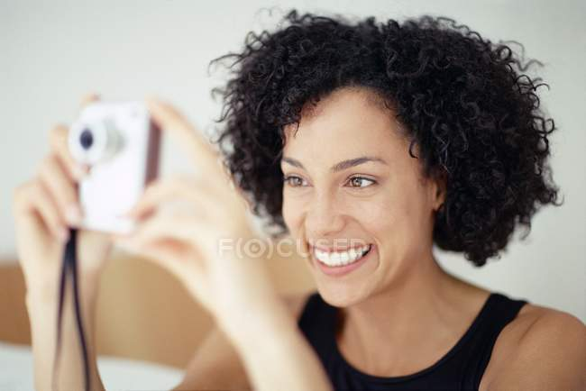 Mixed race woman taking picture with camera and smiling. — Stock Photo