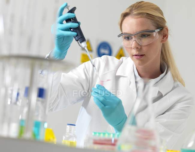 Female researcher pipetting liquid in science laboratory. — Stock Photo