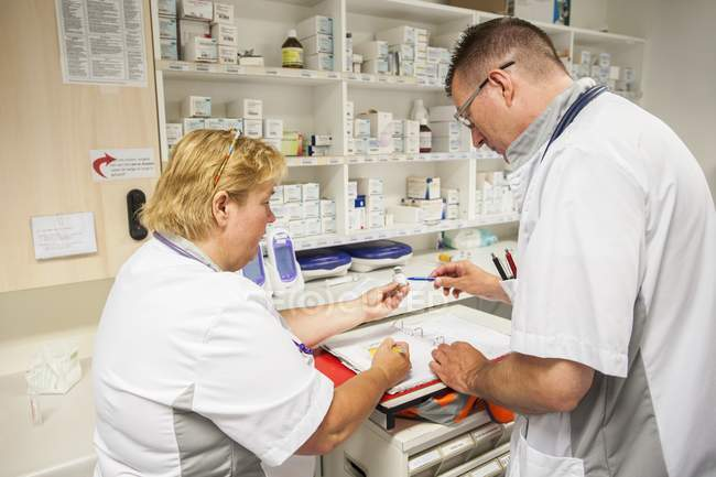 Male and female nurses preparing drugs. — Stock Photo