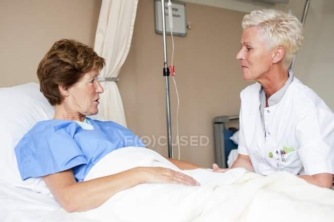 Enfermeira e paciente na cama conversando no hospital . — Fotografia de Stock