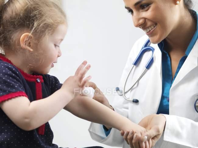 Женщины педиатр, очистка рана на руке дошкольника девочки. — стоковое фото