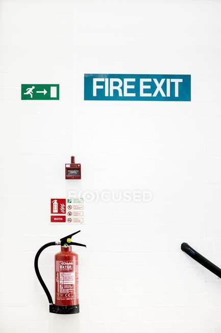Огнетушитель, пожарная сигнализация и знаки пожарного выхода на белой стене . — стоковое фото