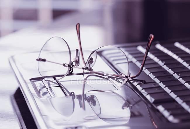 Nahaufnahme von Gläsern auf Laptop-Tastatur. — Stockfoto