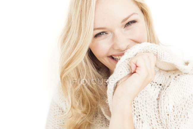 Young woman smiling and covering face with sweater. — Stock Photo