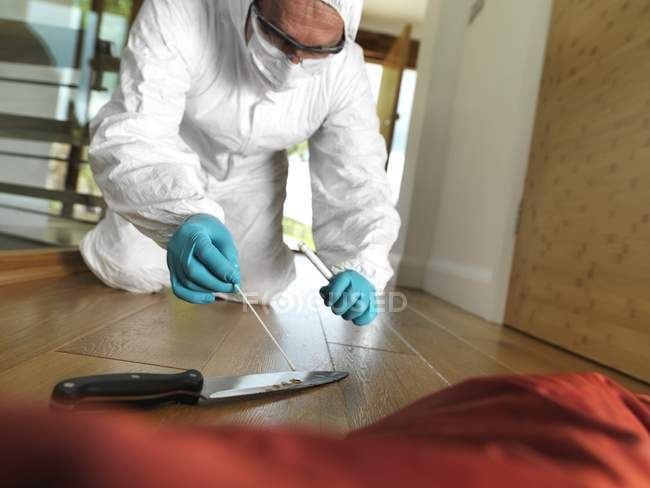 Forensic scientist at scene of crime collecting DNA sample from knife as forensic evidence. — Stock Photo
