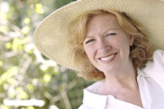 Atractiva mujer madura en sombrero grande - foto de stock