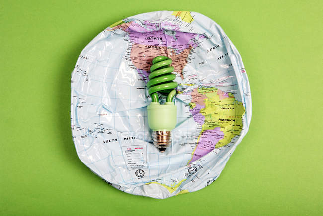 Spiral light bulb on deflated Earth globe, green energy concept. — Stock Photo