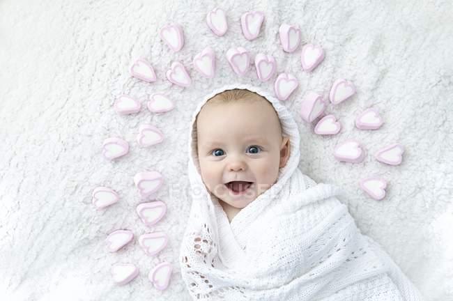 Мальчик, завернутый в одеяло с сердцами вокруг головы . — стоковое фото