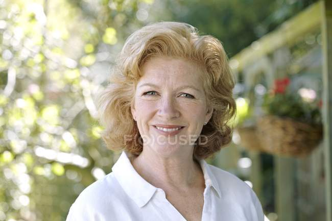 Attractive mature woman standing outdoors — Stock Photo