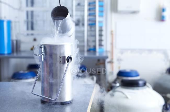 Рідкий азот, виливши в каністру cryostorage. — стокове фото