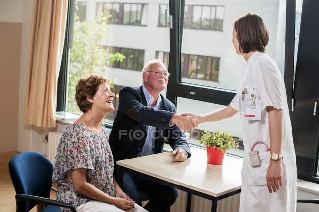 Doctor meeting with senior patients in hospital. — Stock Photo