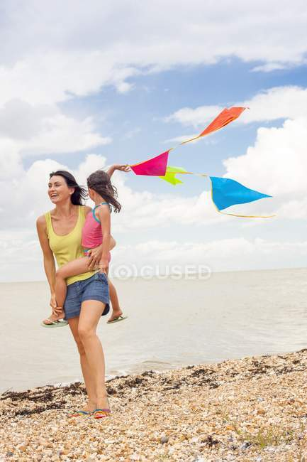 Mother carrying daughter holding bunting on beach. — Stock Photo
