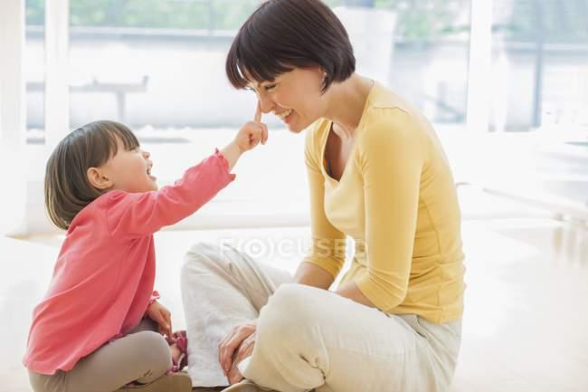 Toddler filha tocando nariz mãe . — Fotografia de Stock