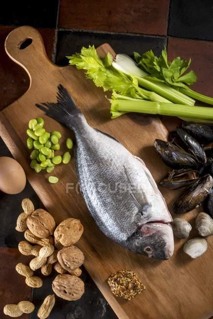 Alimentos alérgenos em tábua de madeira — Fotografia de Stock